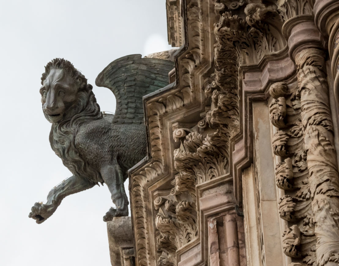 High in the air among the gargoyles, the lion looks like he's stepping off into space, and he's not happy about it.